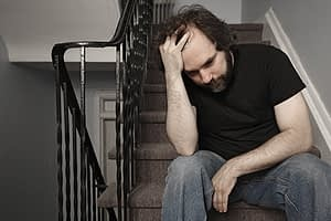 Man sitting on stairs with hand to head going through vicodin withdrawal