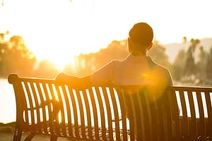 Man sitting on bench in sunshine of detox centers in South Florida