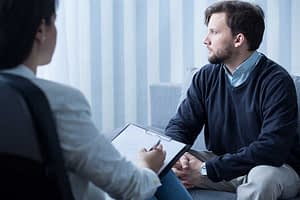 Man talking to counselor during his addiction treatment for professionals