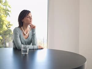 Serene woman reveling in her sober recovery with a glass of water.