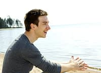 Smiling man on beach after inpatient drug rehab in Florida.