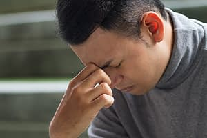 Man with hand to forehead dealing with symptoms of withdrawal from stimulant drugs.