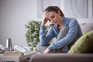 Sad woman on couch trying to get through rapid detox by herself.
