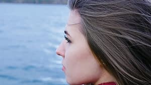 Sad young woman looking out over the water feeling meth withdrawal.