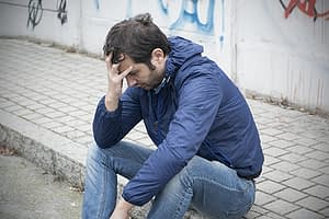 Distressed man on curb worried about suboxone abuse
