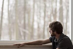 Man at rehab window suffering from anxiety and addiction