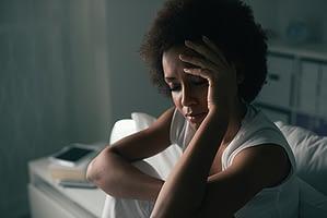 Woman in dark bedroom dealing with opiate withdrawal symptoms.