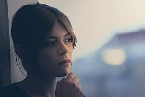 Woman in dark by window wondering about crystal meth detox