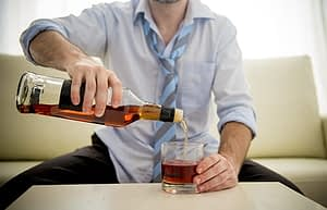 Man in tie pouring a drink should know is alcohol a stimulant or depressant.
