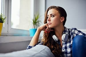 Sad woman looking out window could use residential detox center for her addiction.