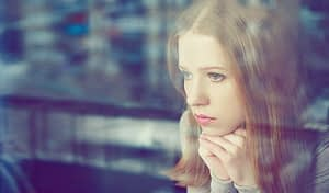 Sad young woman at window worried about her last opioid overdose.