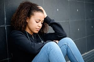 Depressed young woman sitting against wall struggling with symptoms of heroin withdrawal.
