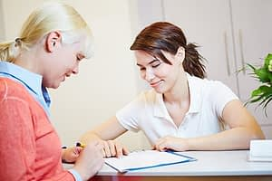 Woman signing in to a rehab for women, with the guidance of a counselor.