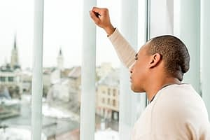 Depressed man looking out window suffering with Pain Pill Withdrawal symptoms