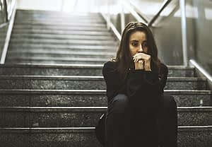 Sad young woman on dark steps suffering with depression from abuse of drugs