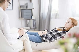 Young woman on a couch talking to counselor during depression treatment