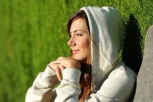 Woman in hoodie enjoying sun during a women's rehab program stay.