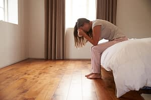 Woman leaning out of bed suffering Adderall side effects of depression and fatigue.