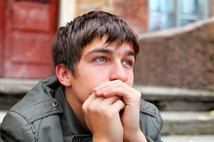 Sad young man on stoop worried about family codependency and trying to quit drugs.