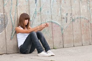 Young women sitting by the fence may be on the fence asking how to detox from meth addiction