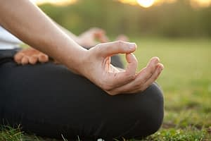 Person outside in meditation pose using meditation for anxiety management