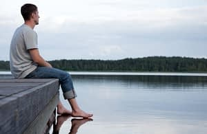 Man sitting on dock wondering when will I be sober