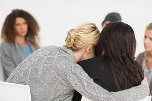 Two women understanding each other at an addiction recovery group.