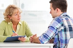 Female counselor explaining psychological addiction to drugs to male client.