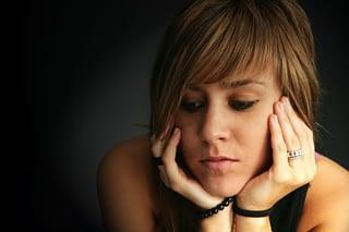 Sad young woman in the dark needs a methadone detox center program