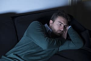 Depressed man in dark dealing with post-acute withdrawal syndrome.