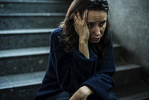 Sad woman on dark steps suffering from one of many mental health disorders.