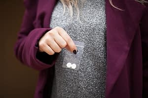 Woman holding small baggie of designer drugs.