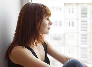 Woman looking out city window needs a fentanyl detox center