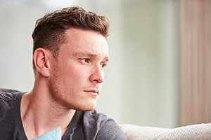Man looking worried when he notices his stages of addiction.