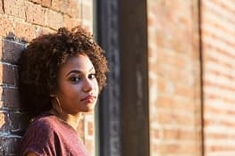 Woman leaning against wall wondering where the best addiction treatment programs are located.
