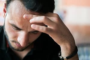 Man with hand on forehead has gotten into trouble with his addictive behaviors.