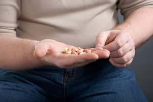 man looking at handful of pills thinking about attending the painkiller detox center