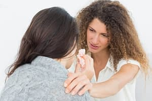One woman consoling another through detox symptoms.