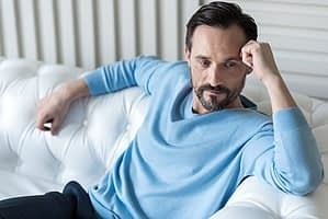 Man on sofa in blue sweater worried about detox protocol for his drug abuse.