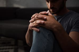 Man in dark wondering about methadone and suboxone for opioid addiction recovery