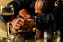 Guy laying on a table passed out with drink in hand, looks like he might need alcohol rehab