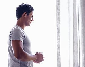 Young man looking out window pondering how long does it take to detox from alcohol