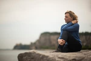 Woman on rock at beach deciding on inpatient vs outpatient rehab for her addiction.