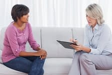 Two women, one a therapist conduct individual therapy.