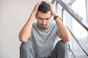 Man struggling with hangover from mixing ecstasy and alcohol