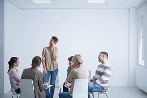 person standing and sharing their story at a group mood disorder treatment center in florida