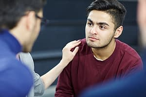 person consoling a man in group therapy at a schizophrenia treatment center