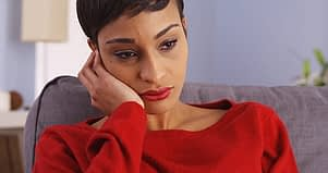 Sad woman in red suffering from a dual diagnosis therapy treatment