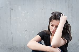 Distressed woman against wall with hangover wants to fix her physical addiction