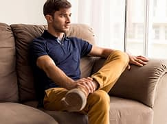 Young man on couch decided whether local detox centers can help him.